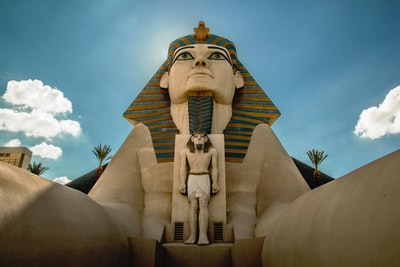 gold statue of man on top of white concrete building pyramids teams background