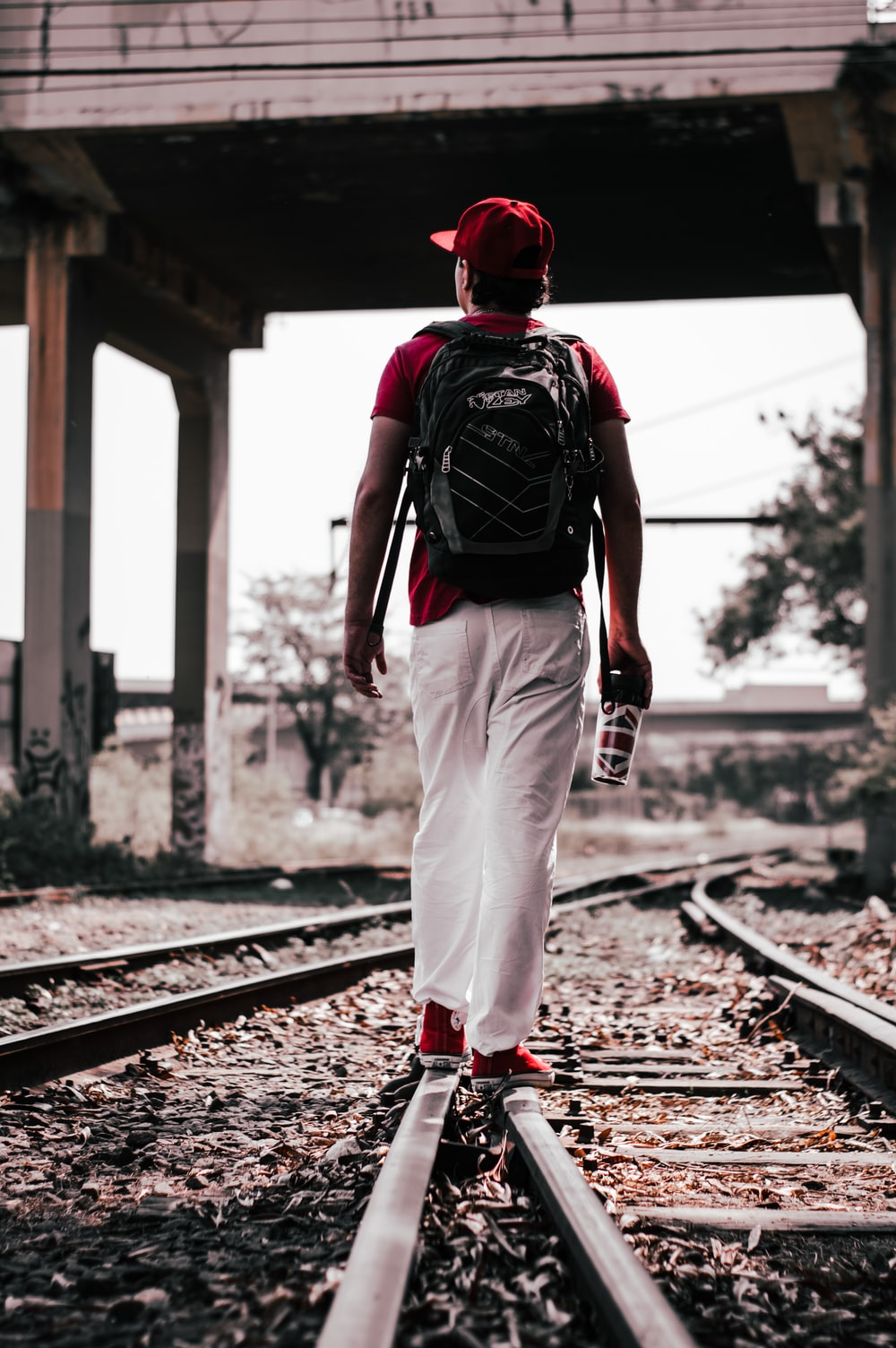 man in red and black backpack walking on train rail during daytime