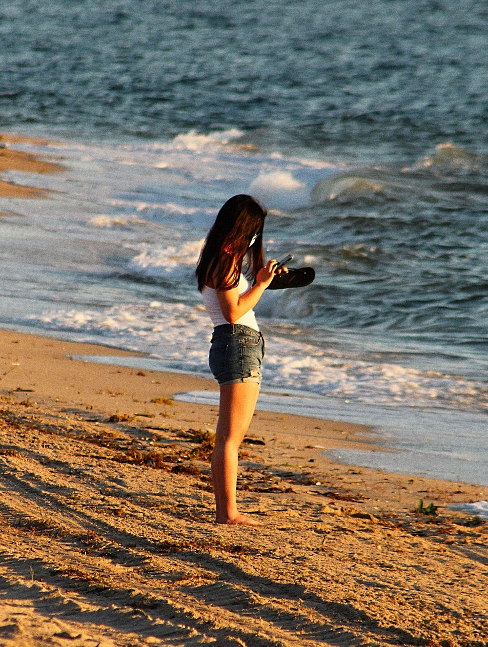 woman in white crop top and blue denim shorts standing on beach shore during daytime