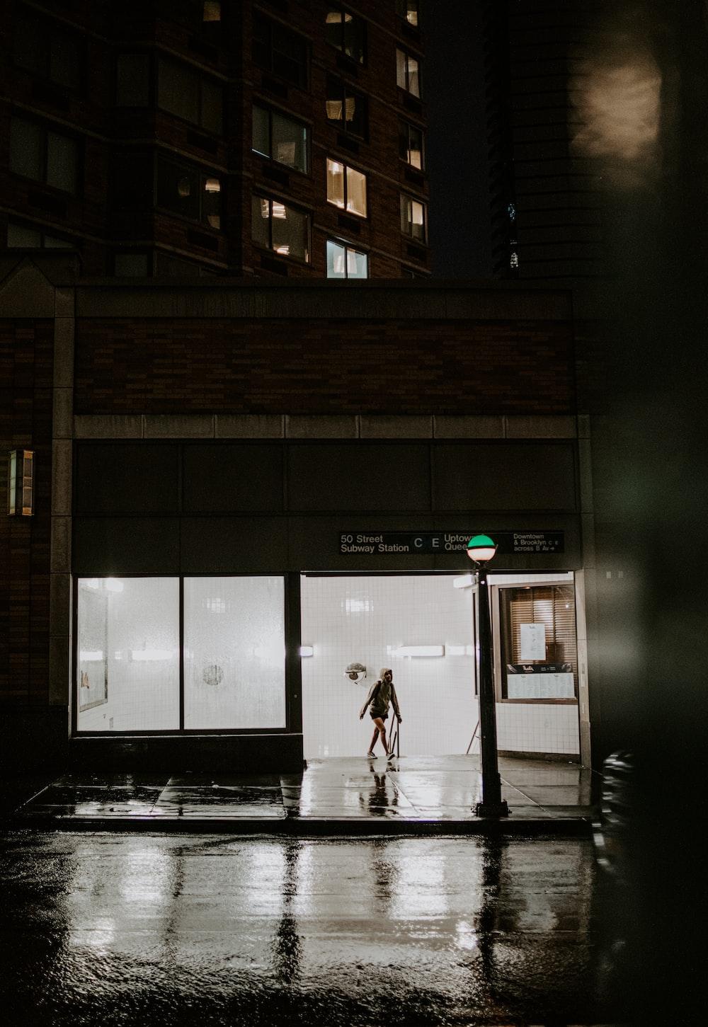 person walking on sidewalk during night time