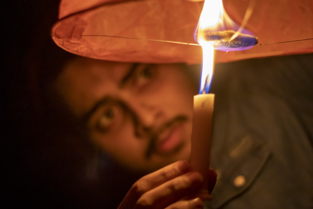 person holding lighted candle in front of man