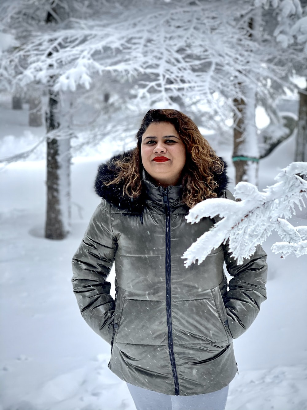 woman in gray winter coat standing on snow covered ground during daytime