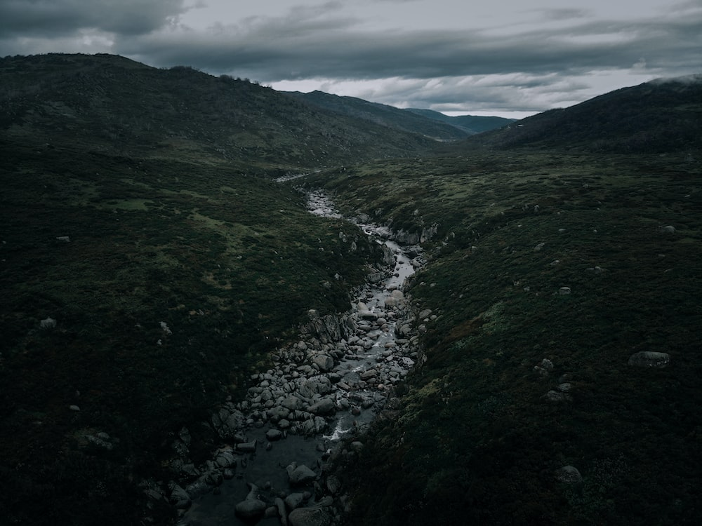 river between green mountains under white clouds during daytime