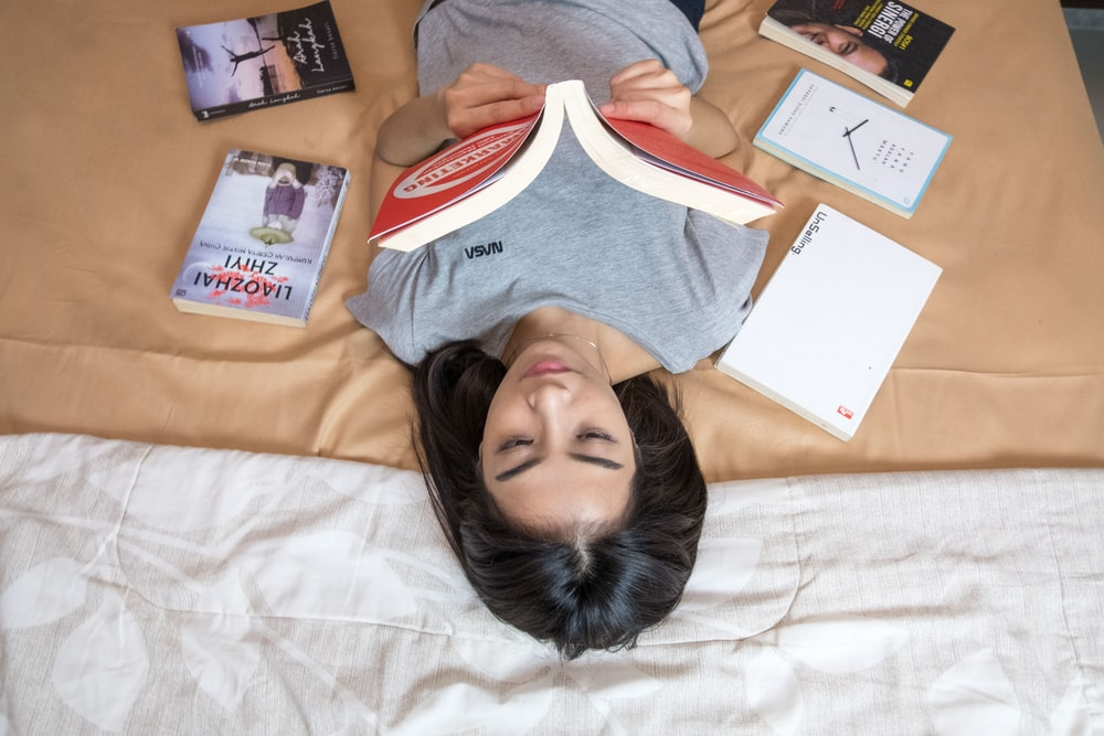 woman in gray shirt lying on bed