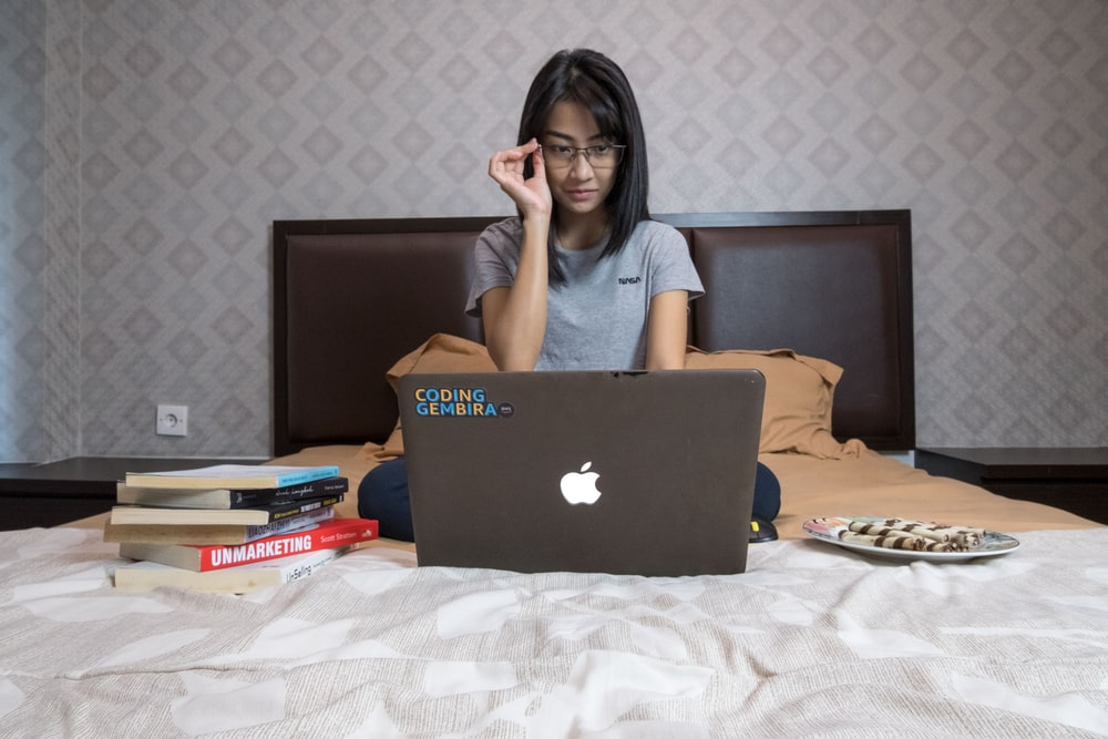 woman in gray shirt sitting in front of macbook
