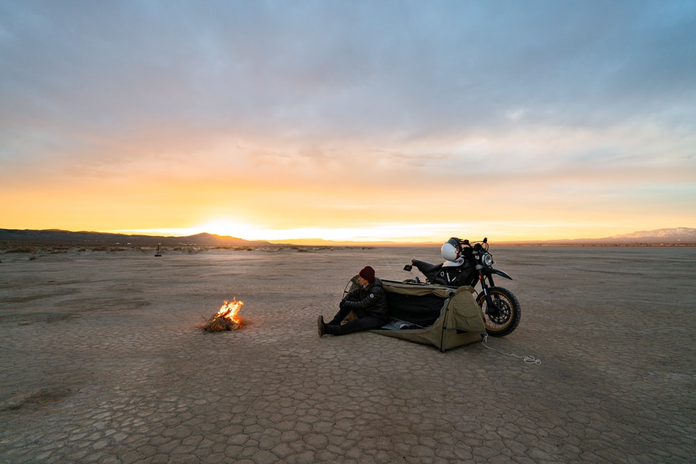 black and white motorcycle on beach during sunset