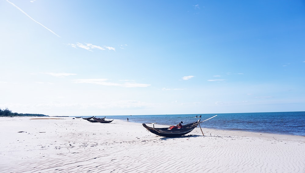 blue boat on white sand beach during daytime