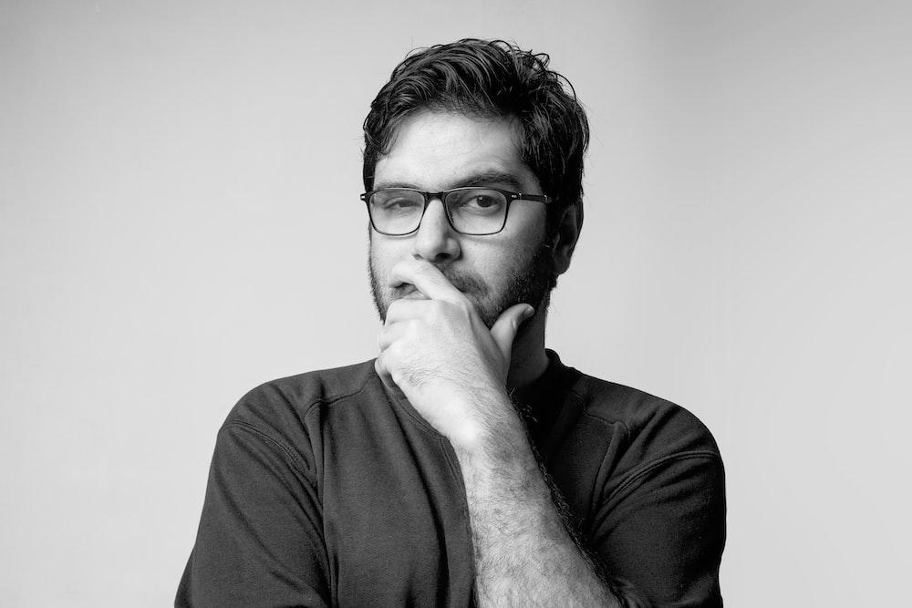 man in black long sleeve shirt wearing black framed eyeglasses