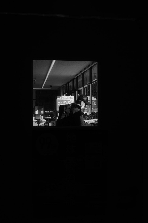 grayscale photo of man in black jacket standing near glass window