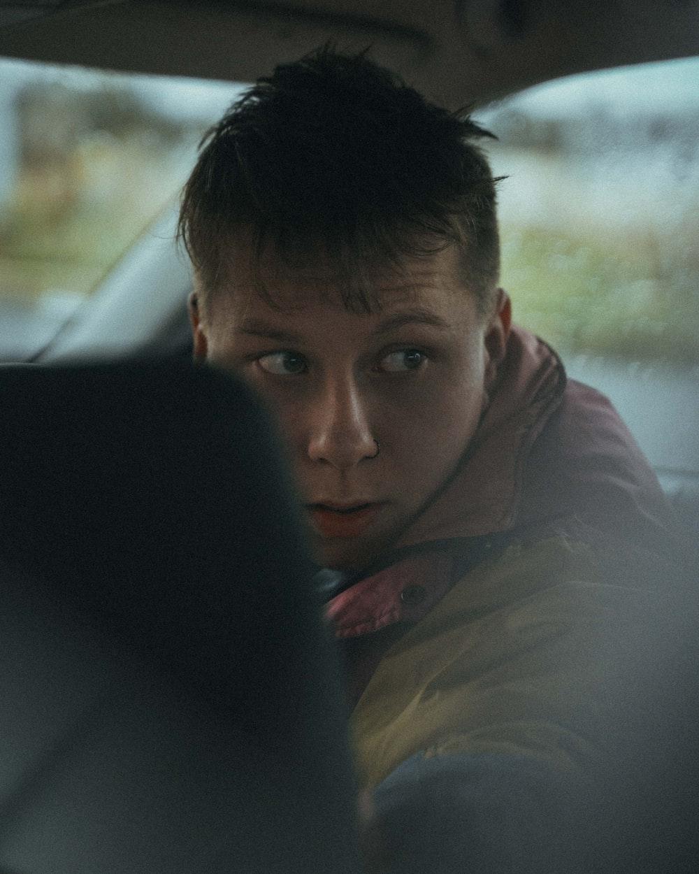 man in brown jacket sitting on car seat
