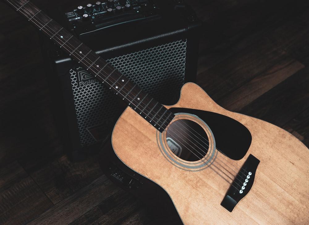 brown acoustic guitar on black guitar case