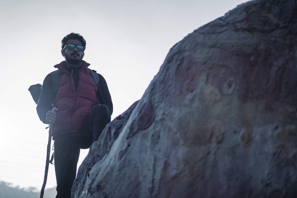 man in blue jacket and black pants standing on rock formation during daytime