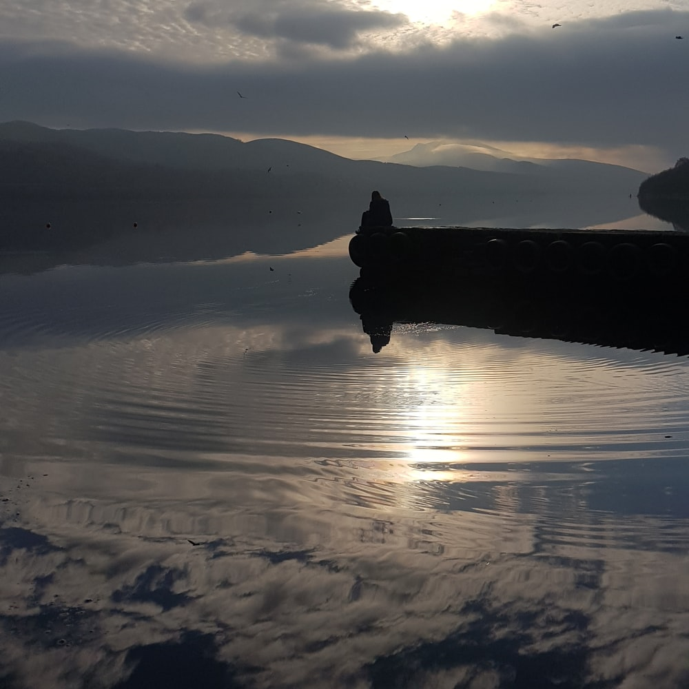 silhouette of man standing on boat on water during daytime