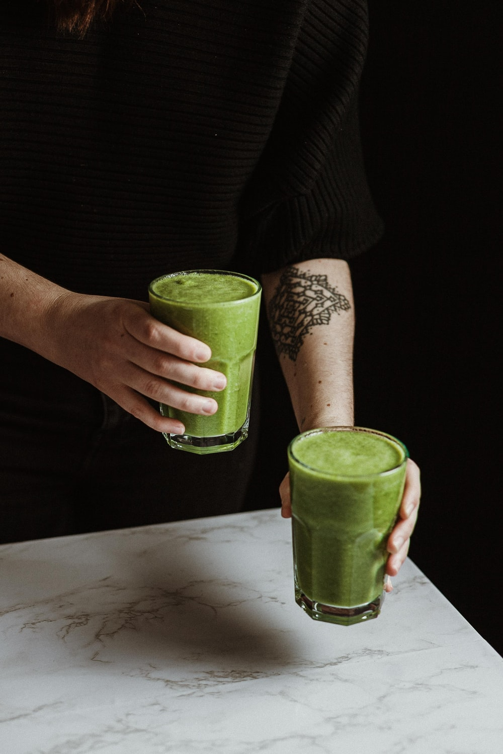 person holding green drinking glass