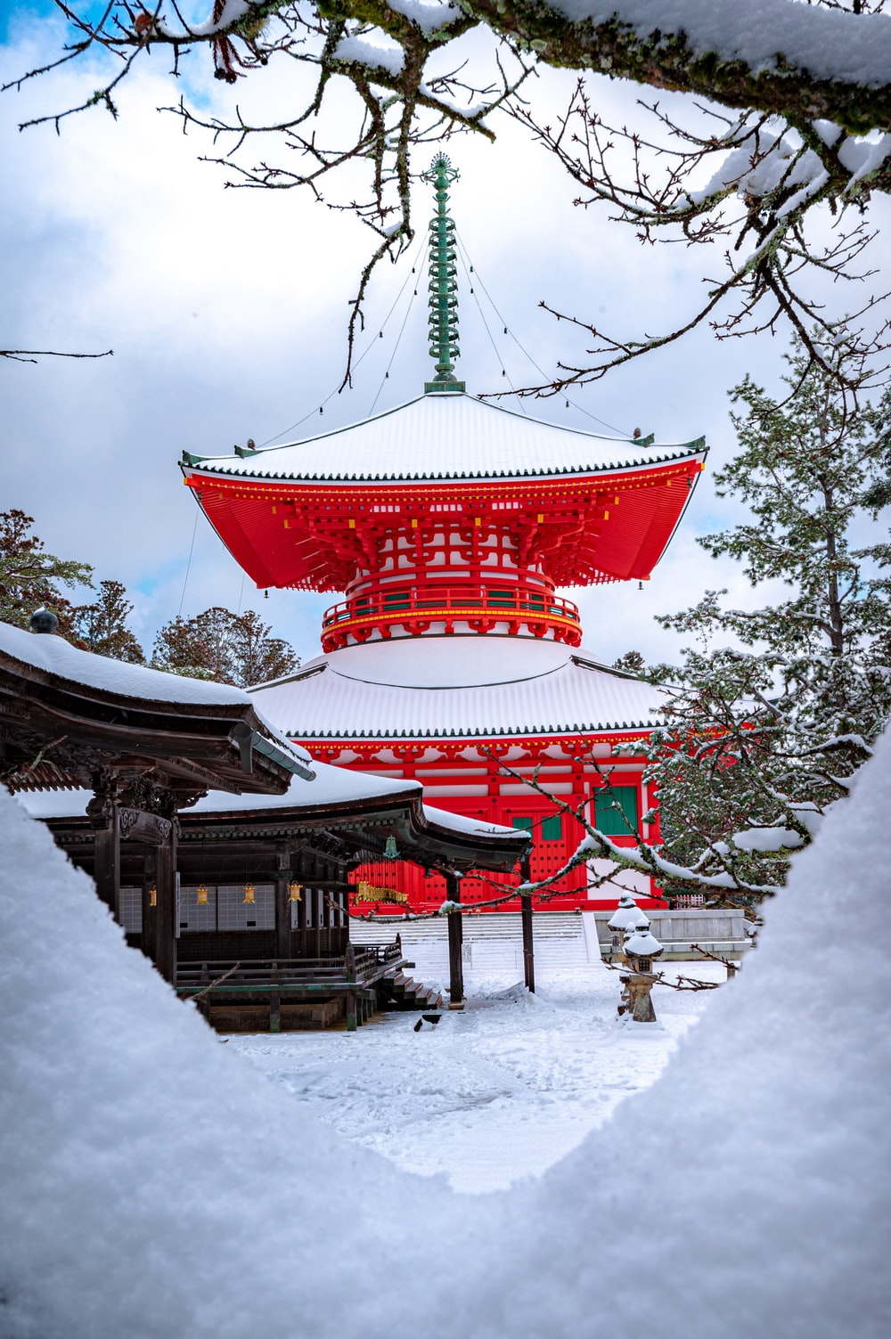 red and white temple surrounded by trees covered with snow