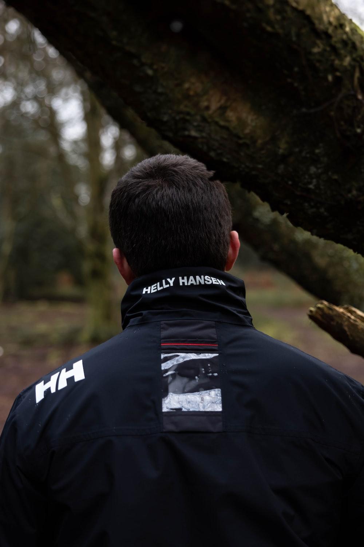man in black jacket standing beside brown tree during daytime