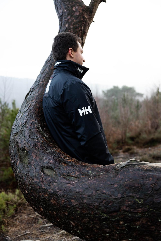 man in black jacket sitting on brown tree trunk during daytime