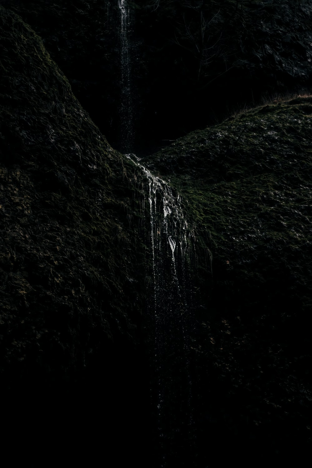 water falls in the middle of green moss