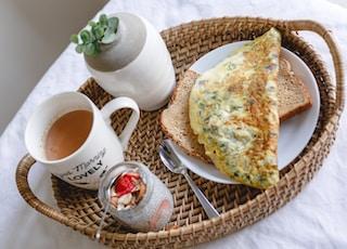 bread with egg on white ceramic plate beside white ceramic mug
