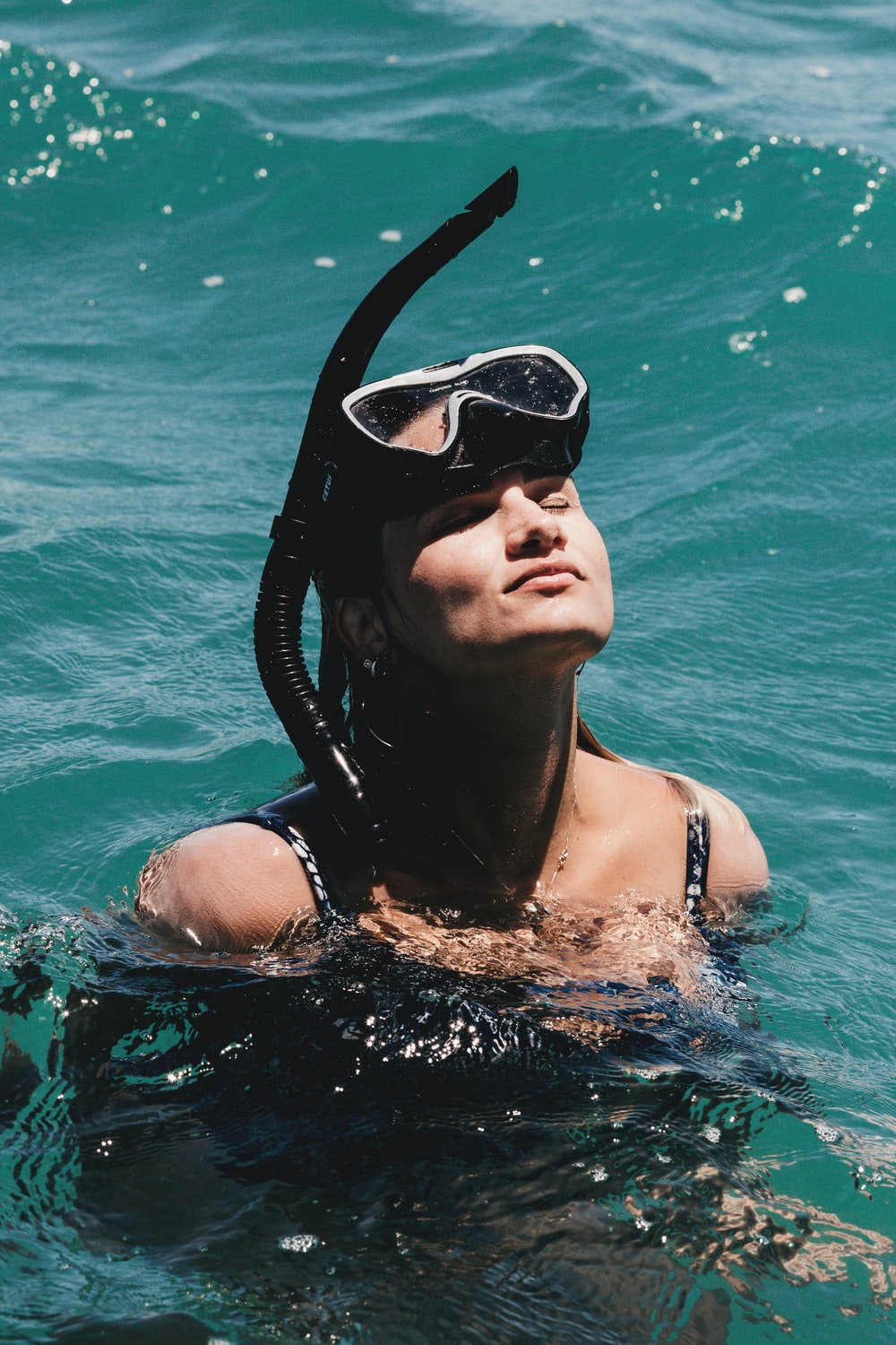 woman in black swimming goggles in water