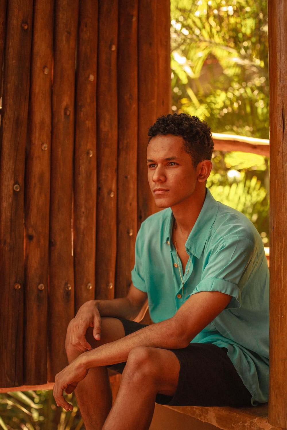man in green button up shirt sitting on brown wooden bench