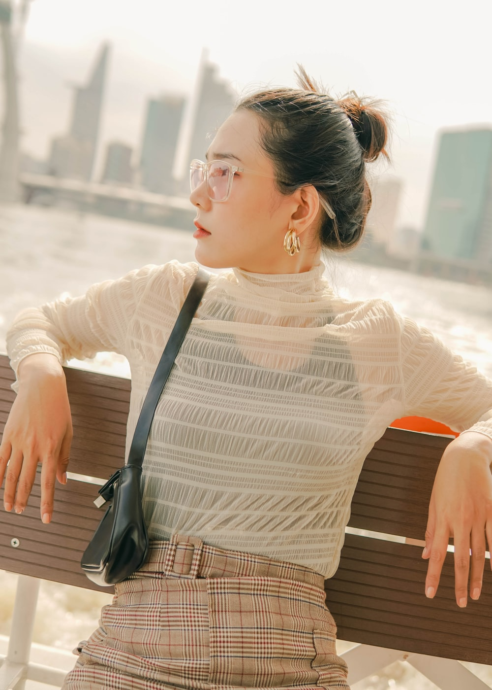 woman in white long sleeve shirt sitting on brown wooden bench