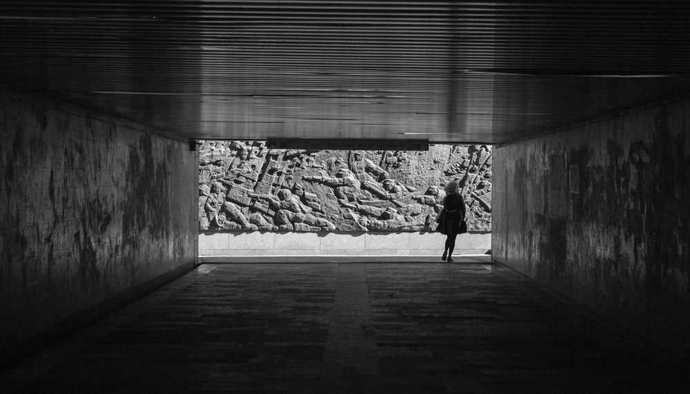 grayscale photo of woman walking on wooden floor