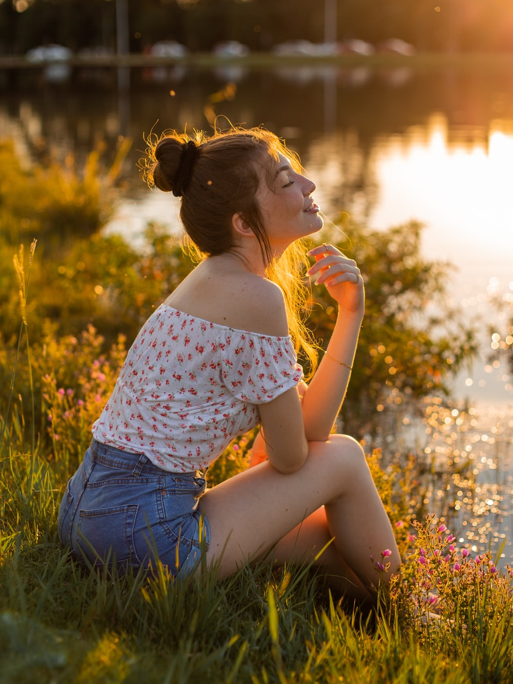woman in white and red floral shirt and blue denim shorts sitting on green grass during