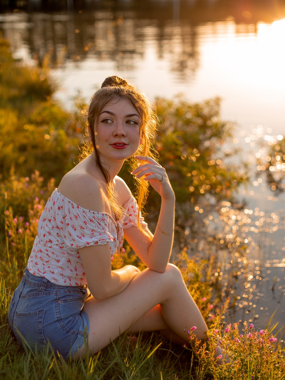 woman in pink and white floral tank top and blue denim shorts sitting on green grass