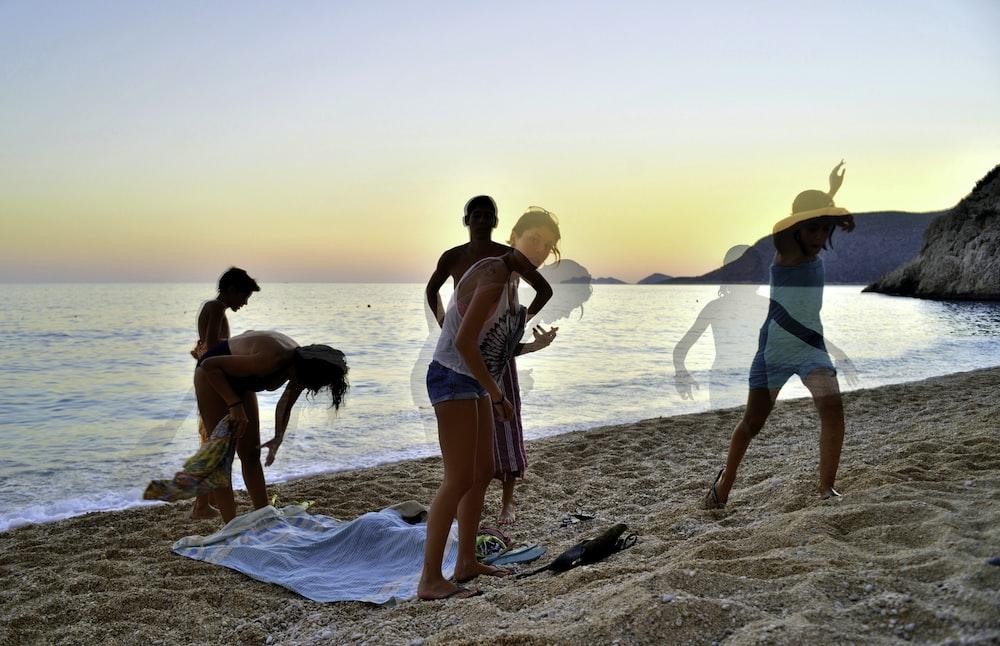 2 women in bikini walking on beach during sunset