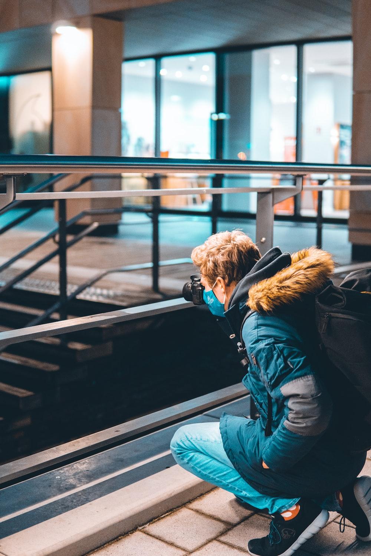 woman in blue denim jacket and blue denim jeans sitting on black metal railings