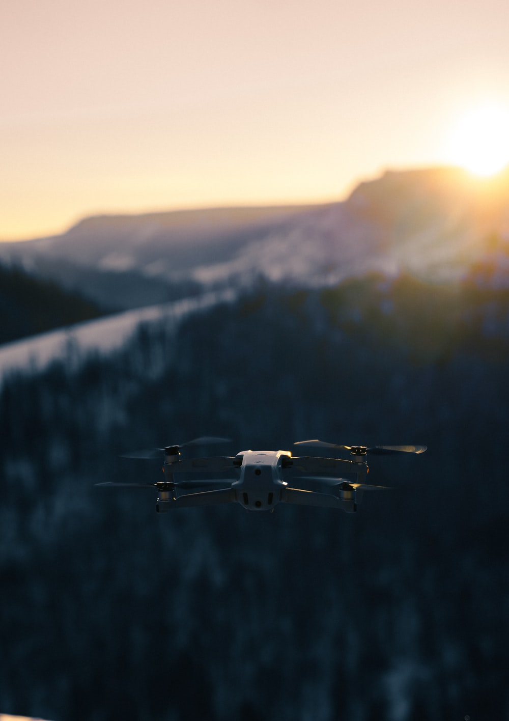 white and black drone flying over the green trees during daytime