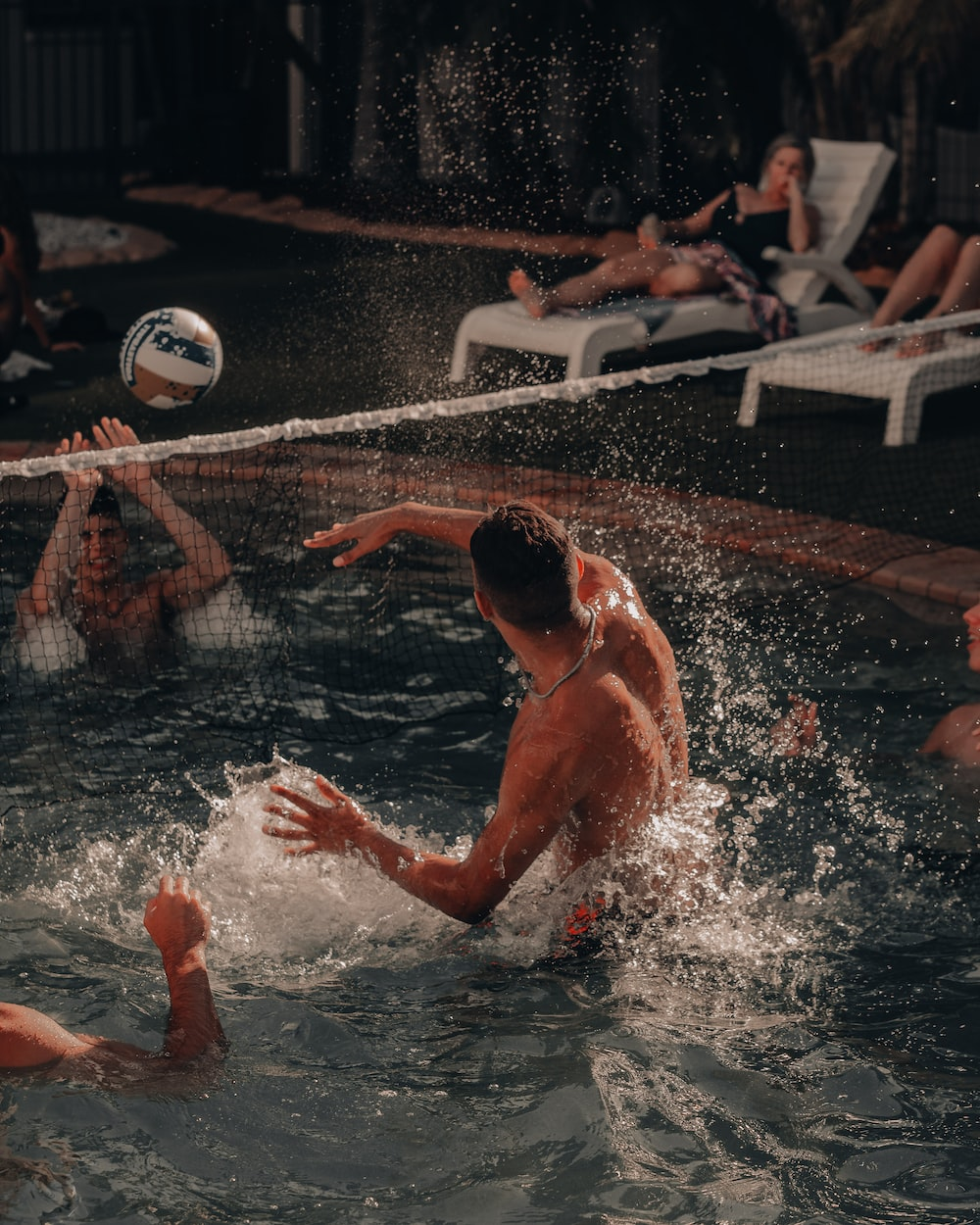 man in swimming pool playing volleyball