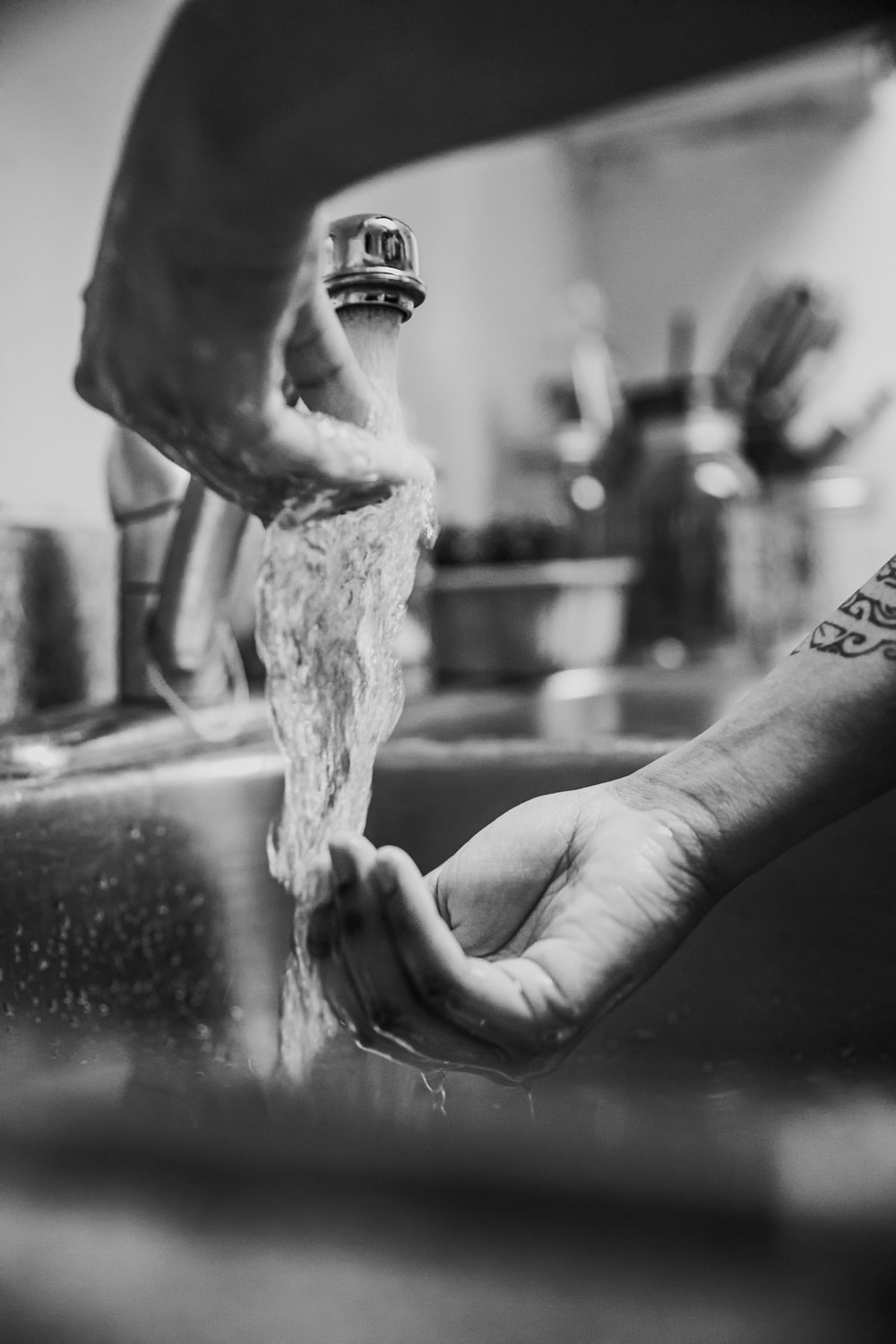 grayscale photo of person pouring water on persons hand