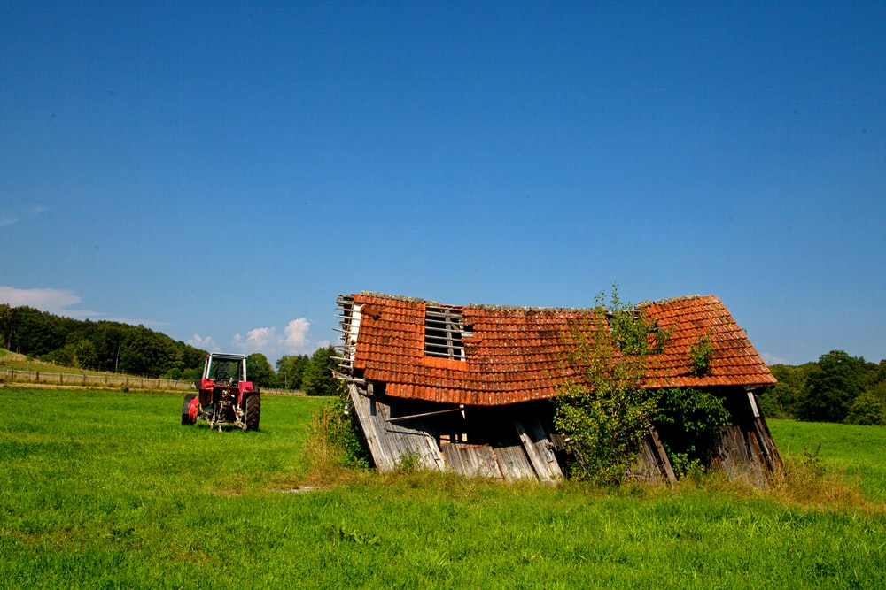 brown wooden house on green grass field under blue sky during daytime