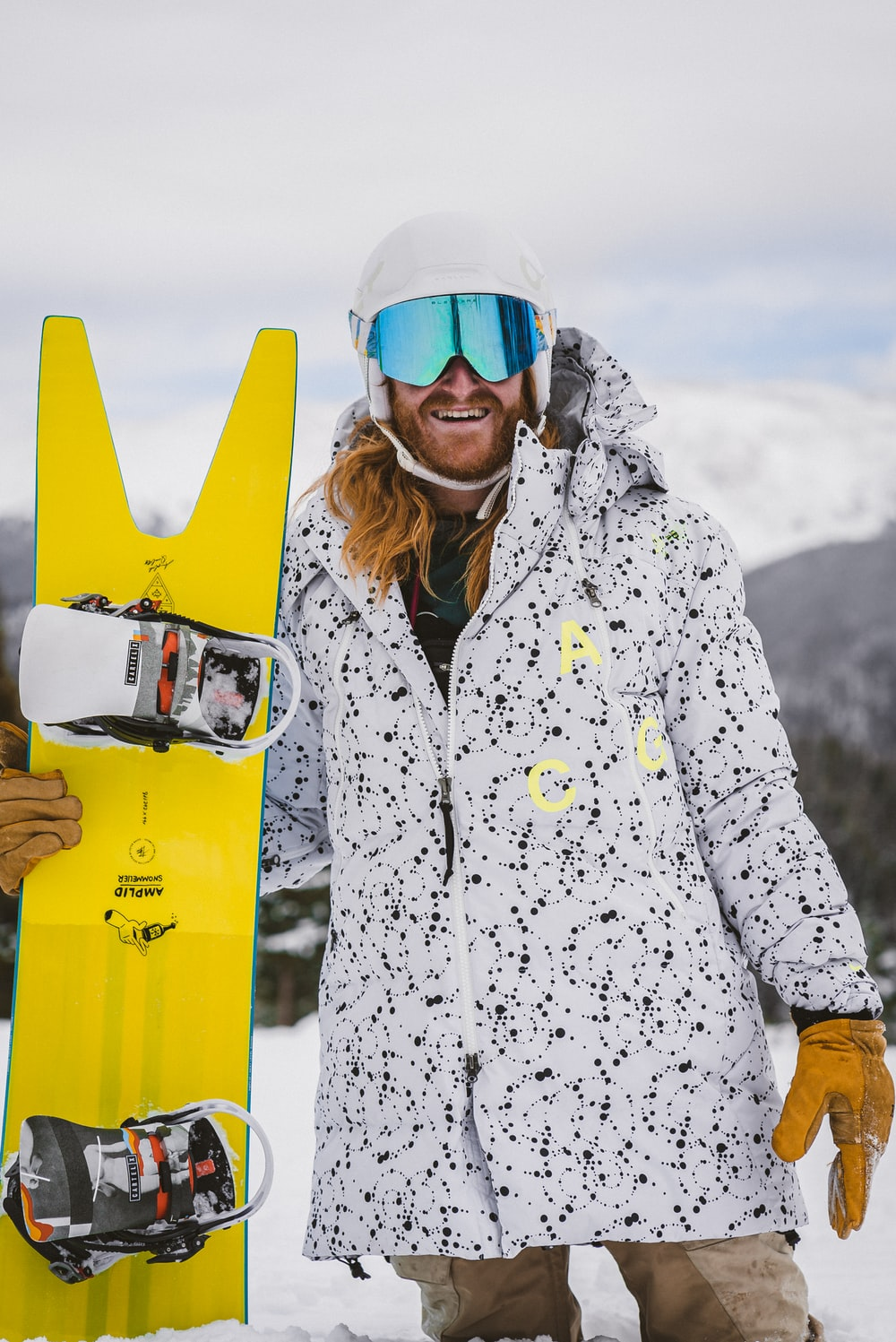woman in white and black snow jacket wearing blue goggles
