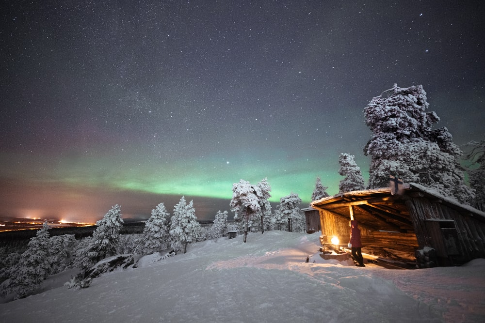 brown wooden house on snow covered ground during night time