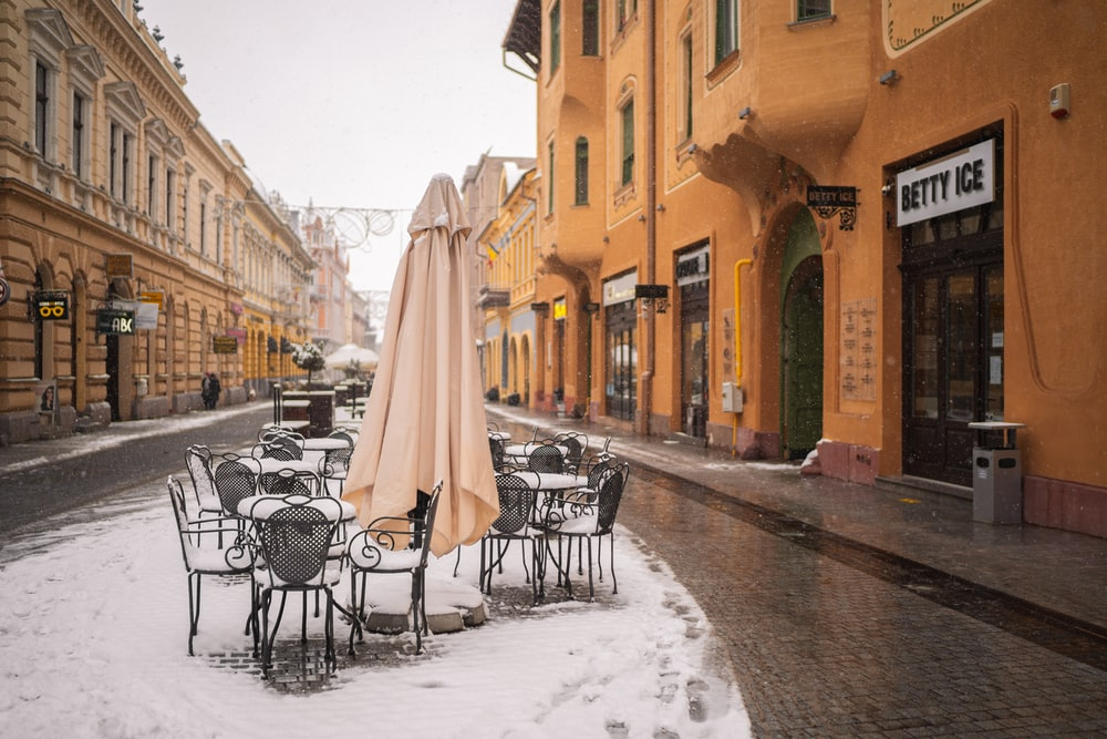 white umbrella on black metal chairs on snow covered ground