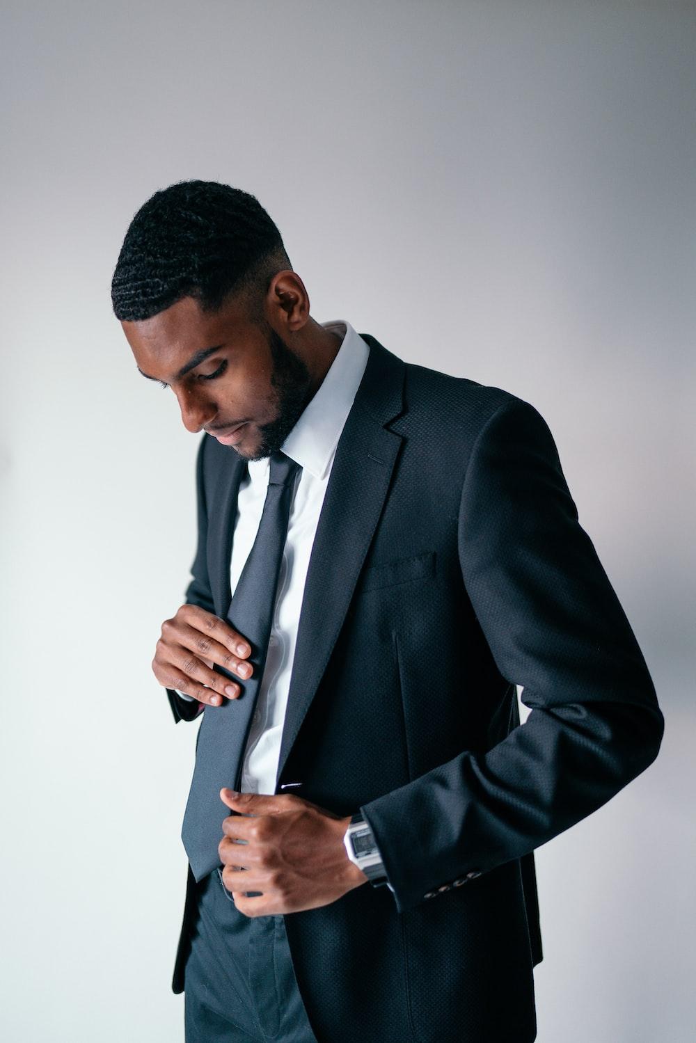 man in black suit holding black smartphone