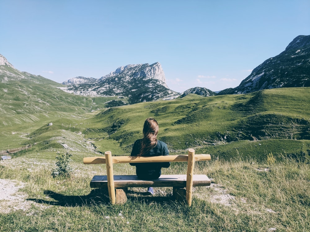 woman sitting on brown wooden bench on green grass field during daytime