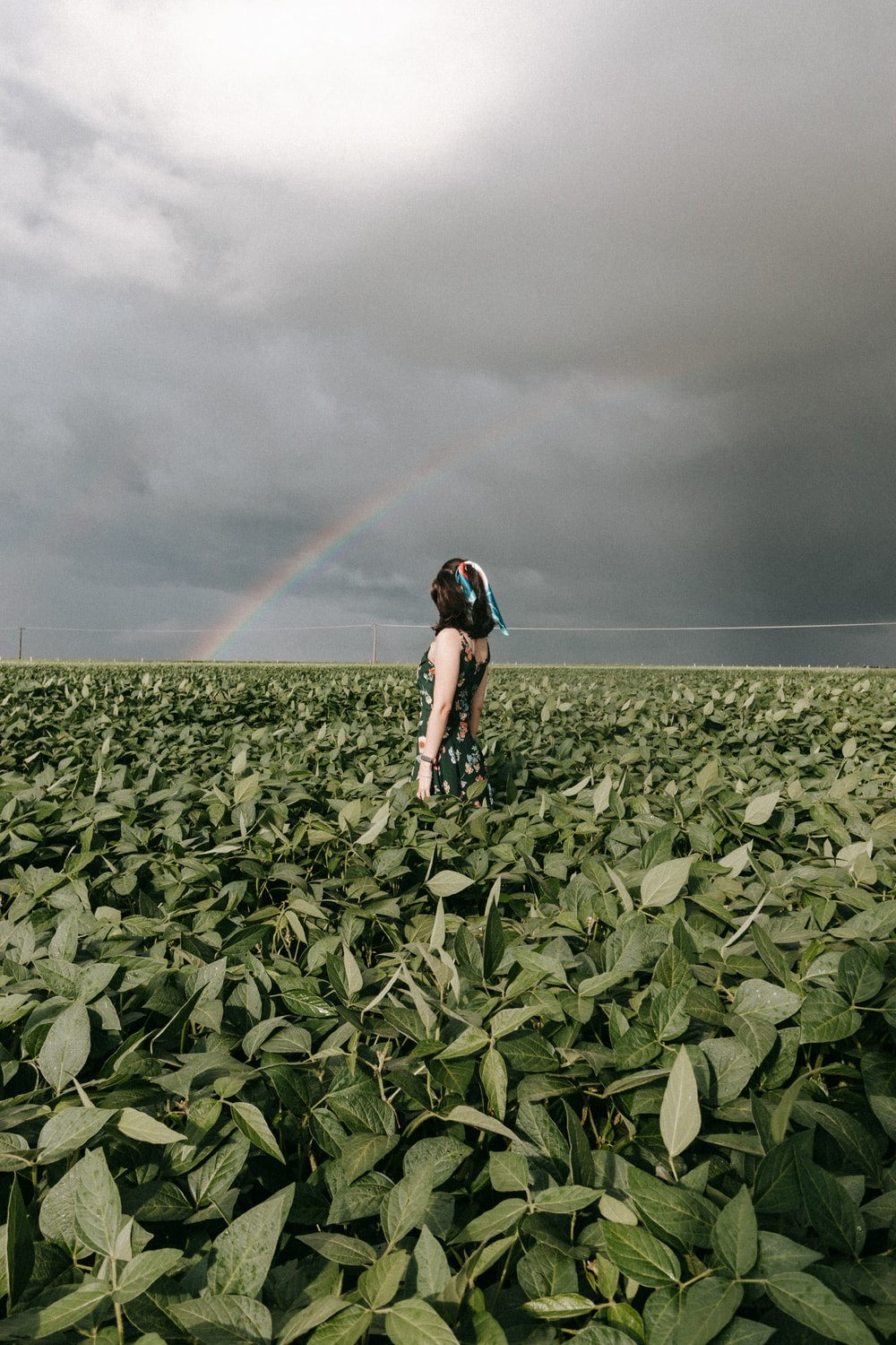 woman in black tank top and black shorts standing on green grass field under gray sky