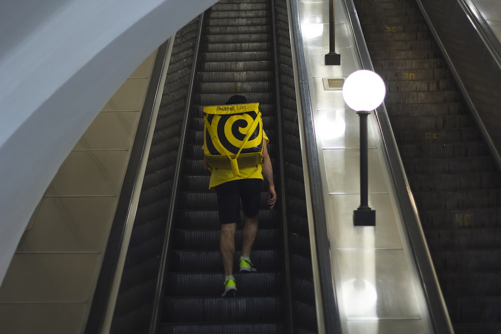 person in yellow and black batman shirt and black shorts walking on black staircase