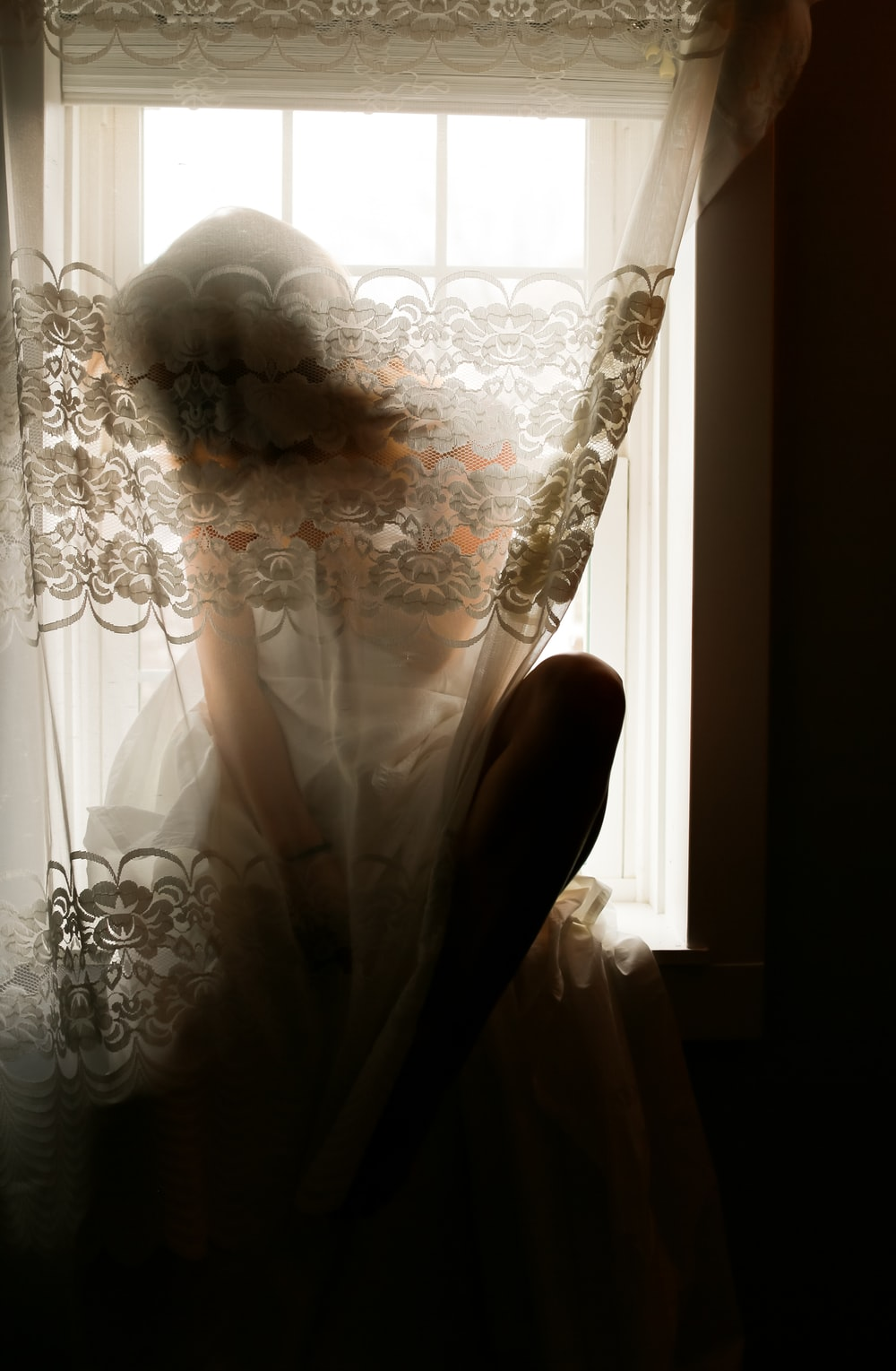 woman in white floral wedding dress sitting on white floral sofa