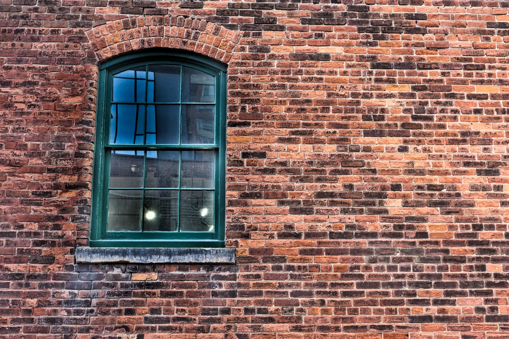 brown brick wall with blue wooden window