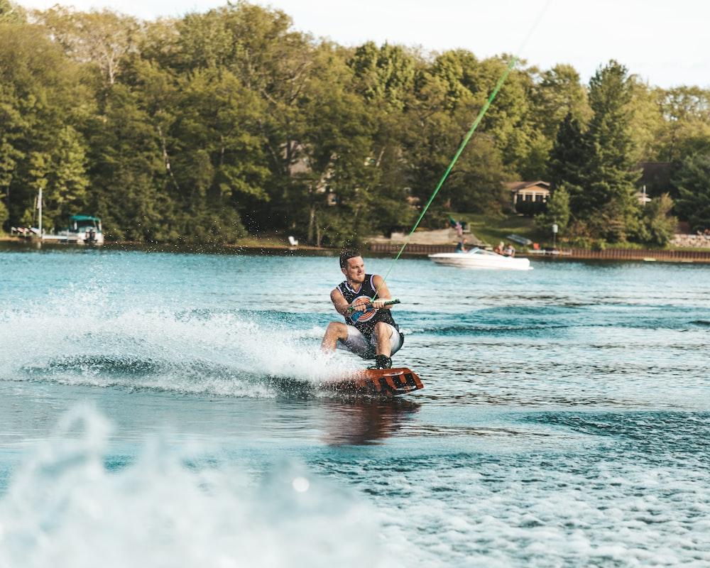 man in red shorts riding red kayak on water during daytime