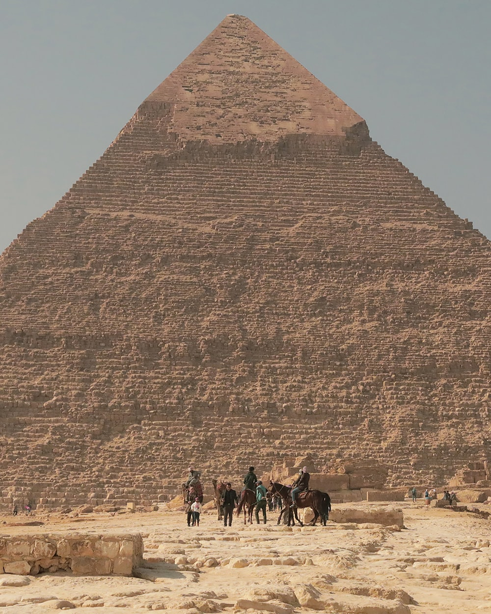 people walking on brown sand near pyramid during daytime