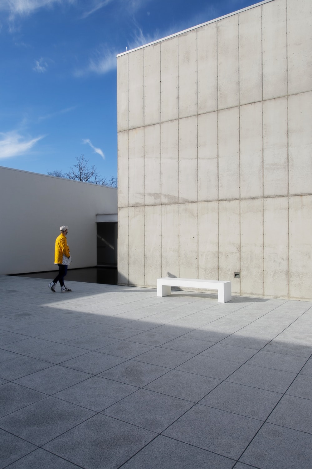 man in yellow jacket and black pants walking on gray concrete floor during daytime