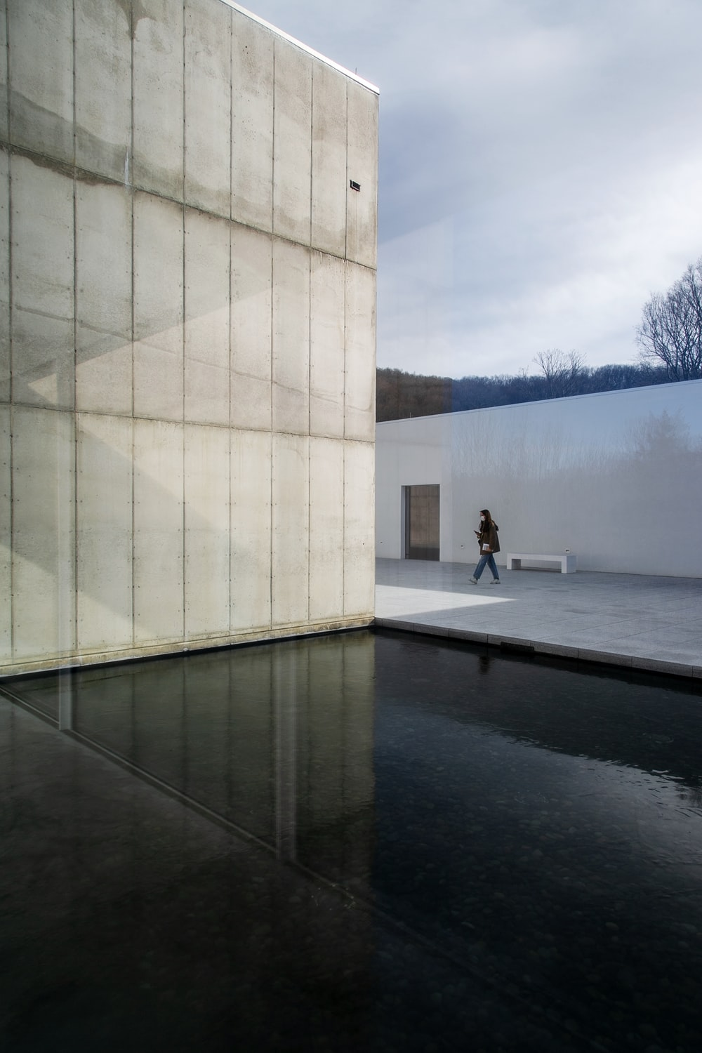 person in white shirt and black pants standing on gray concrete floor near white concrete building
