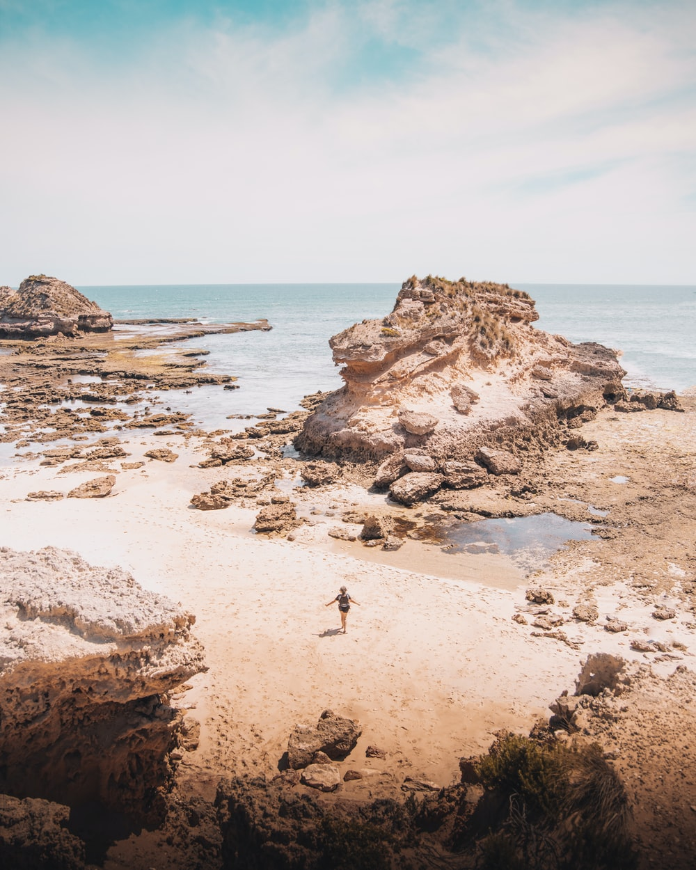 person standing on brown rock formation near body of water during daytime