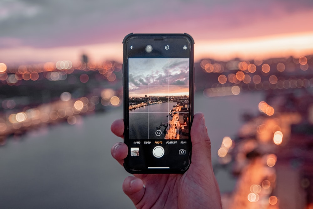 person holding black iphone 5 taking photo of city during sunset